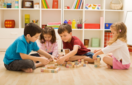 Four children playing with blocks on the floor
