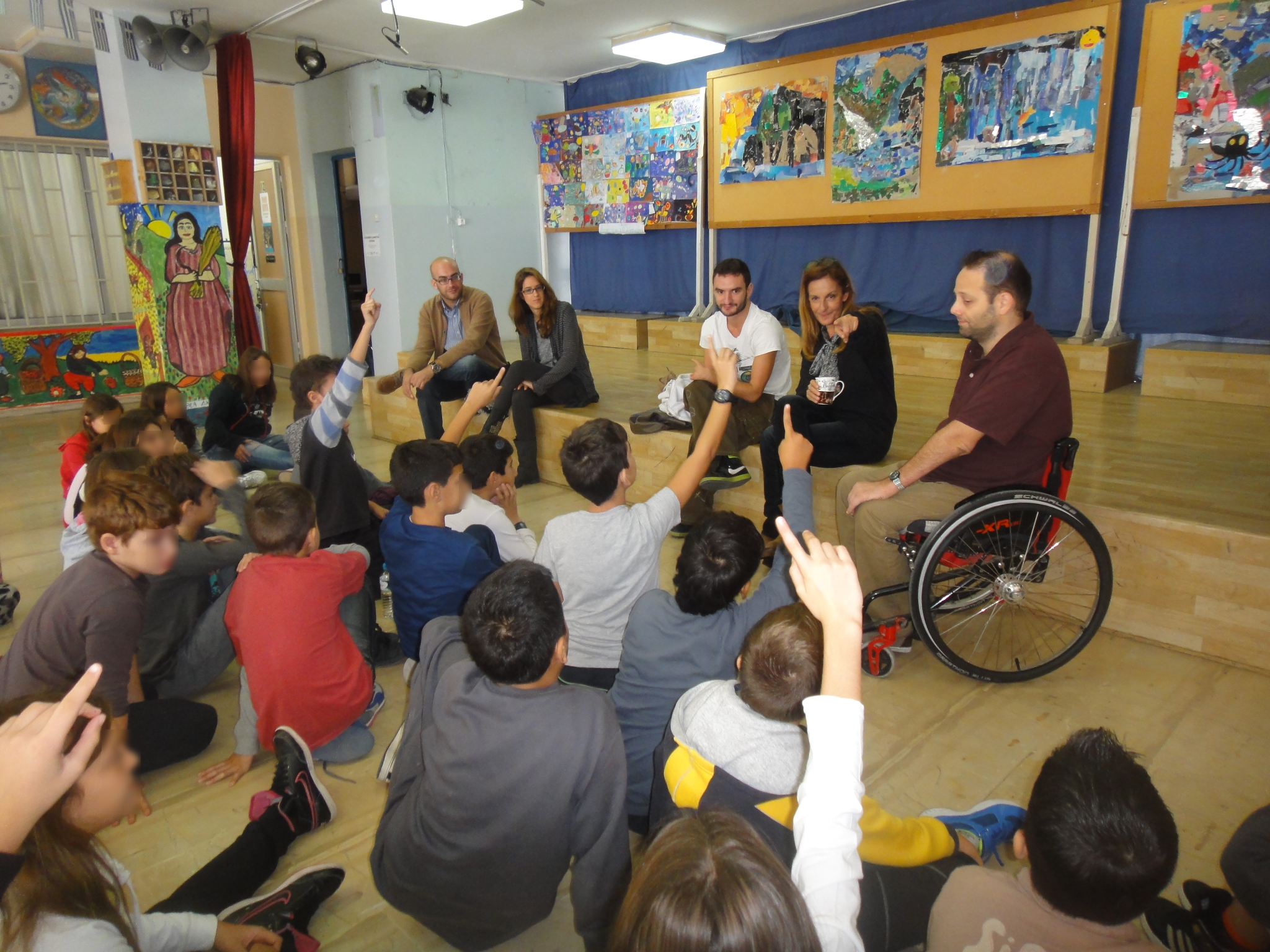 A man in a wheel chair giving a presentation to a group of students
