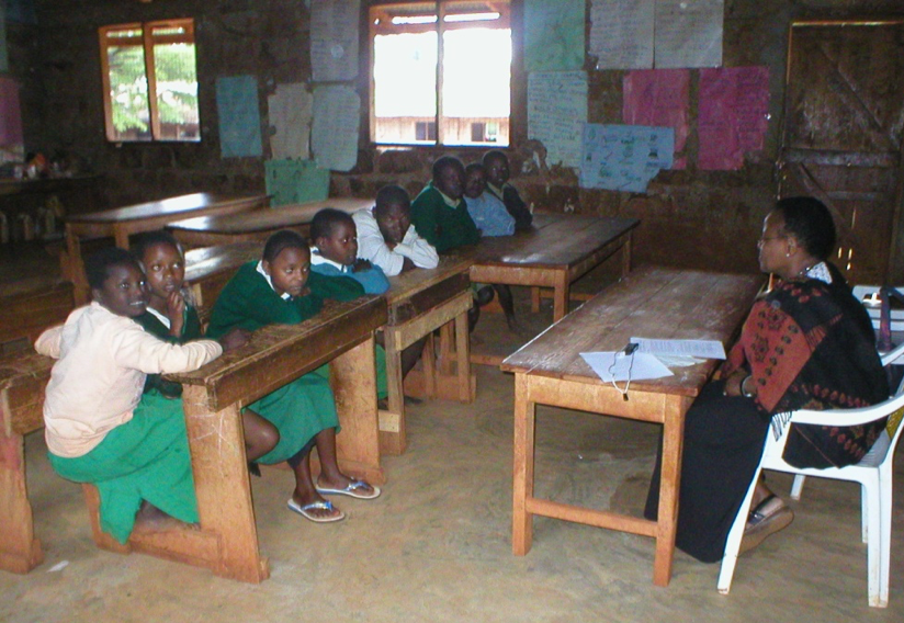 A number of students in a classroom sitting at their desks and a teacher at a teacher desk in front