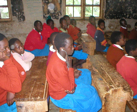 Students in red sweaters and blue skirts or pants sitting at desks in their classroom