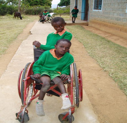 a child pushing another child in a wheelchair