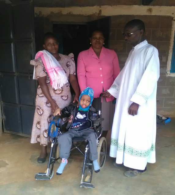 A child in a wheelchair in the centre and three adults behind him